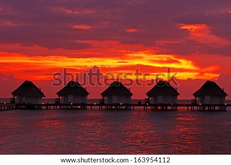 Water Villas (Bungalows) on the Perfect Tropical Island after sunset in Maldives - stock photo