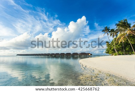 Water Villas (Bungalows) on the Perfect Tropical Island, Beautiful white sand on Tropical beach blue water blue sky with coconut palm , Maldives islands  - stock photo