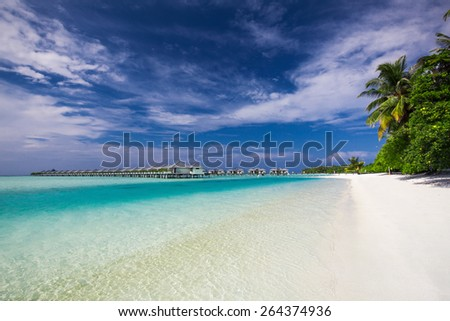 Water Villas (Bungalows) on the Perfect Tropical Island in Maldives with clean beach - stock photo