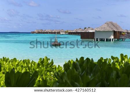 Water villas on the tropical island at Maldives - stock photo