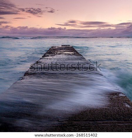 Water washing over a breakwater on famous Waikiki beach in Honolulu Hawaii. - stock photo