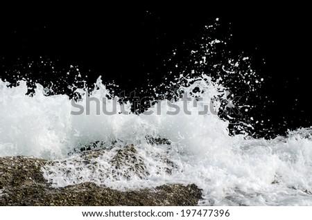 Water wave splashes, isolated on black background - stock photo