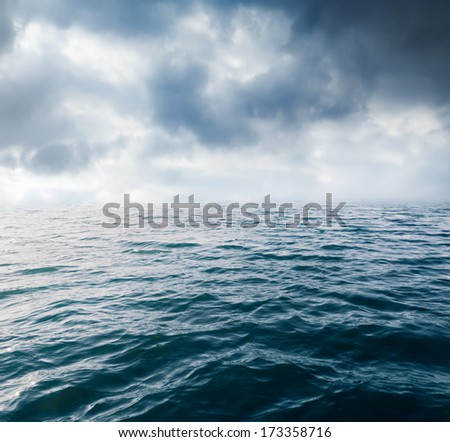 Water waves on cloudy sky background - stock photo