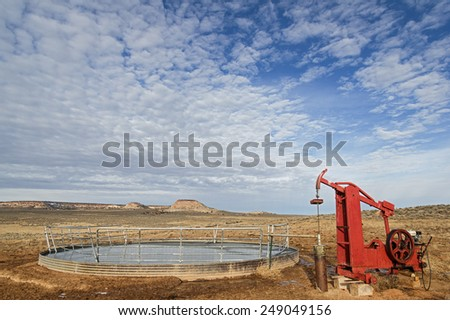 water well and pump filling a frozen over stock tank - stock photo