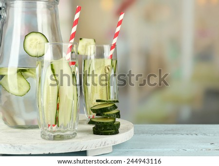 Water with cucumber on wooden table and bright background - stock photo