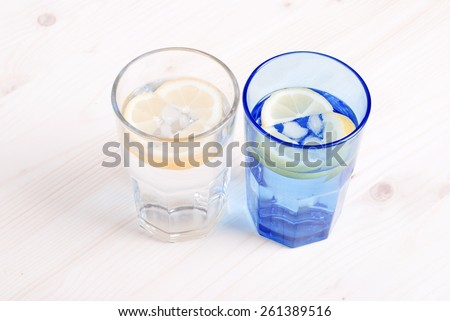 water with lemon and mint in blue glass on  table top view - stock photo