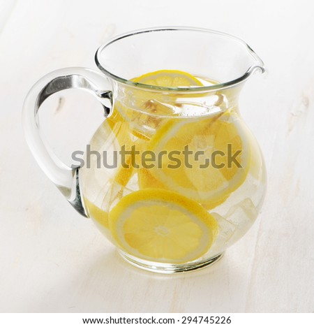 Water with lemon in glass jug. Selective focus