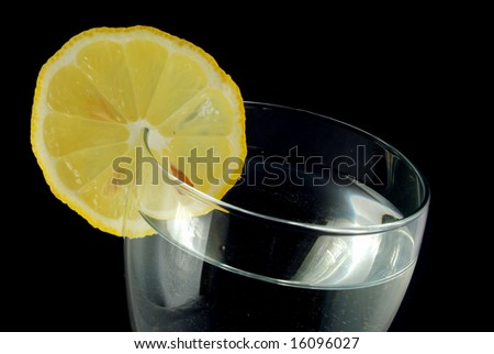 Water with lemon in glass on the black background - stock photo