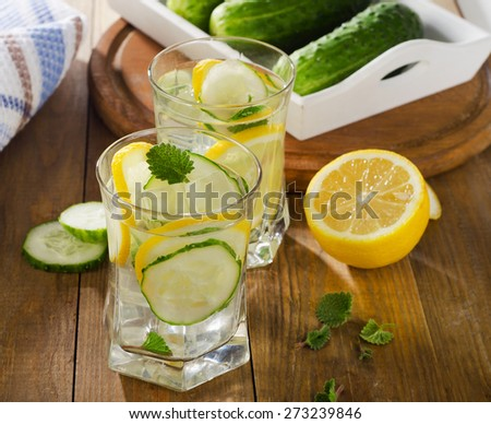 Water with lemon, mint  and cucumber  on  wooden background. Selective focus - stock photo