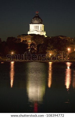 Water with reflection of South Dakota State Capitol and complex at night, Pierre, South Dakota - stock photo