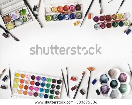 Watercolor and brushes at white background. Flat lay, top view - stock photo
