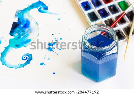 Watercolor jar with a blue tinted water in it. Watercolor paints and drawing of blue seahorse in the background - stock photo