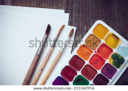 Watercolor paints and brushes, painting tools on an old wooden board. - stock photo