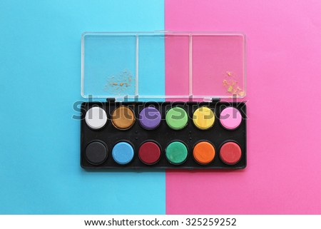 Watercolor paints box on half pink half blue background - stock photo