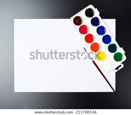 Watercolor set and brush on the white paper sheet over the black surface as a copyspace background composition - stock photo