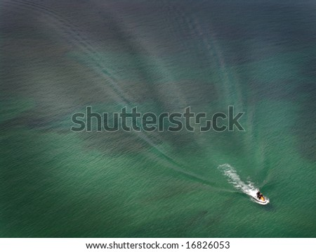 Watercraft making waves on a blue-green lake. - stock photo