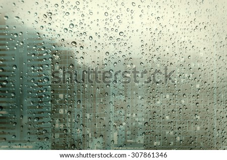 Waterdrops on a glass surface windows with closeup cityscape background - stock photo