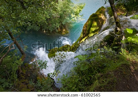 Waterfall and green water of Plitvice lakes viewed through trees