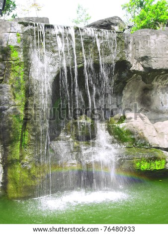 Waterfall and rainbow in park - stock photo