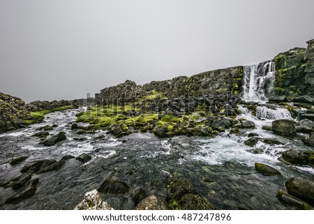 Waterfall and rocks. Cloudy summer day in Iceland