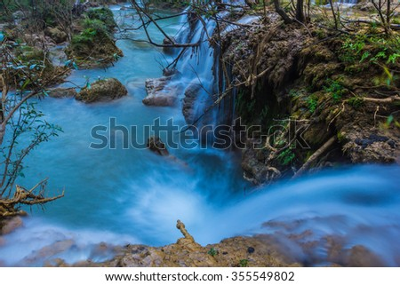 Waterfall close up in forest with stones and stream - stock photo