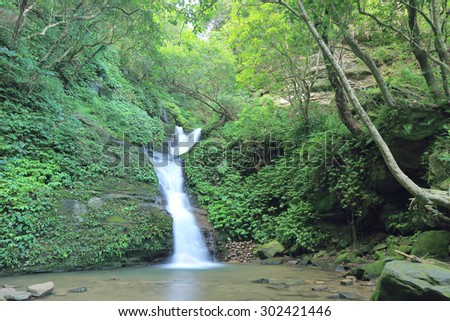 Waterfall in a secret ravine ~ Cool refreshing cascades in a mysterious forest of lush greenery - stock photo