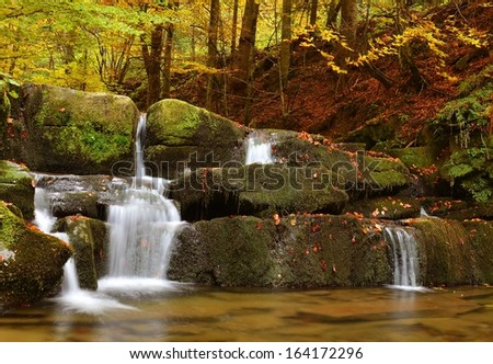 Waterfall in autumn forest scenery - Bieszczady mountains - Poland - stock photo