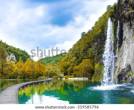 waterfall in autumn mountain forest - stock photo