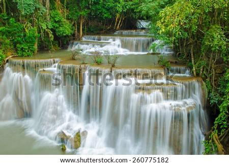 Waterfall in deep rain forest jungle (Huay Mae Kamin Waterfall in Kanchanaburi Province, Thailand). - stock photo