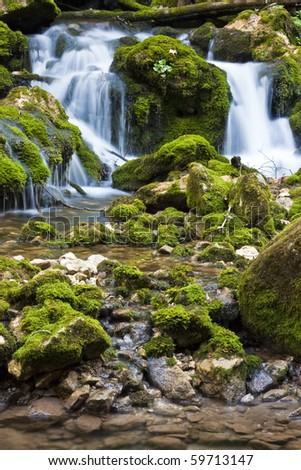 Waterfall in forest with moss on rocks - stock photo
