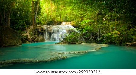 Waterfall in forest with sunlight beams and rays through trees and green leaves  - stock photo