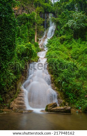 Waterfall in spring season located in deep rain forest jungle.  - stock photo