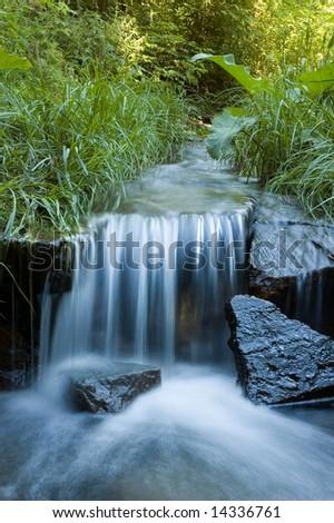 Waterfall in summer garden - stock photo