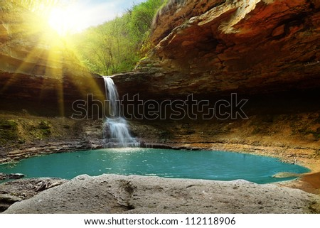 Waterfall in the mountains illuminated by the sun - stock photo
