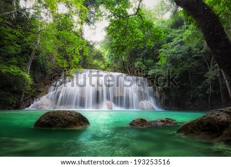 Waterfall in tropical forest. Beautiful nature background. Jungle trees and blue water of mountain river in national park in Thailand, Asia - stock photo