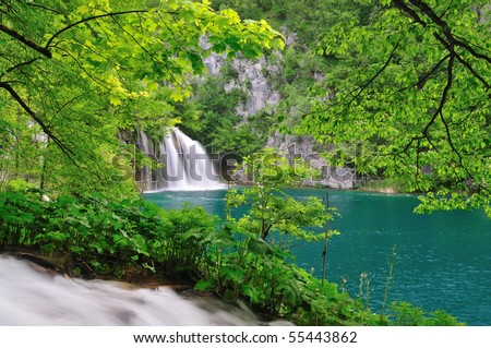 Waterfall into a green lake. Creek and branches of a tree as foreground. - stock photo