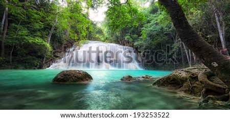 Waterfall landscape background. Beautiful nature outdoor photography. Thailand green rain forest jungle with trees and bushes, fresh clean and cool water river flows through stones cascades - stock photo
