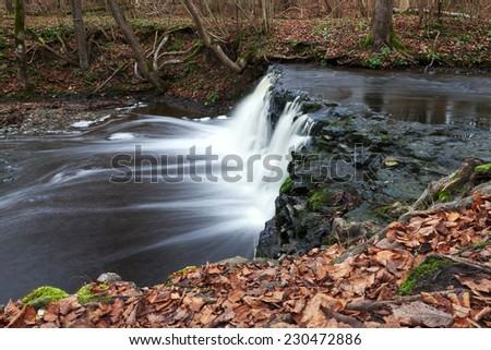 Waterfall on small river in autumn time.