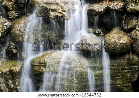 Waterfall over natural stones in japanese zen garden - stock photo