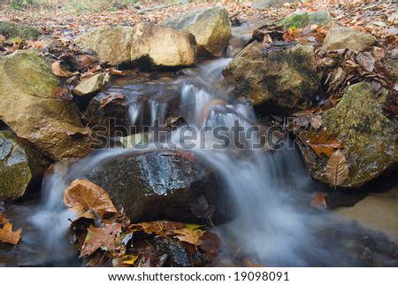 Waterfall over rocks in autumn with long exposure