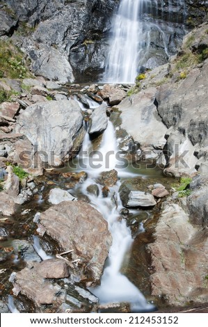 waterfall surrounded by vegetation in Andorra La Vella - stock photo