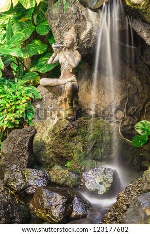 Waterfall with Balinese statue and lush greenery - stock photo