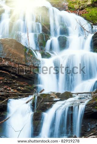 Waterfalls on Rocky Stream, Running Through Autumn Mountain Forest, and sunshine - stock photo