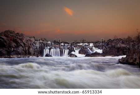 Waterfalls on the Potomac river near Washington DC after sunset as the setting sun illuminates the clouds over Great Falls - stock photo