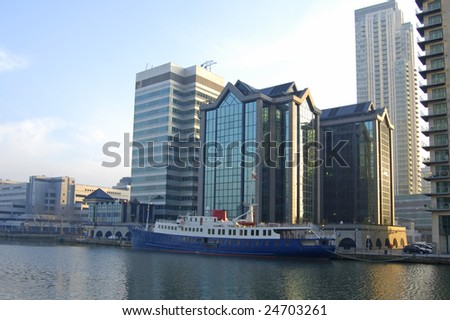 Waterfront buildings and boat at Canary Wharf in London, England - stock photo