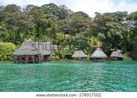 Waterfront ecolodge with thatched hut overwater and luxuriant tropical vegetation on the land, Caribbean side of Panama, Central America - stock photo