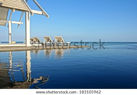 waterfront villa with relaxing chairs by the sea - stock photo