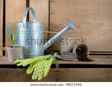 Watering can and gardening tools on wooden crates with wooden crates for background. - stock photo