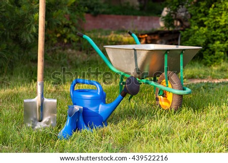 watering can and rubber boots. Garden tools on a green lawn.