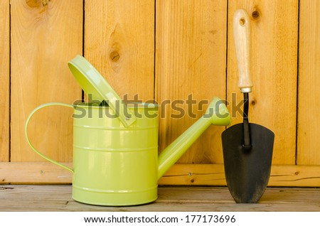 Watering can and trowel on wood background. - stock photo